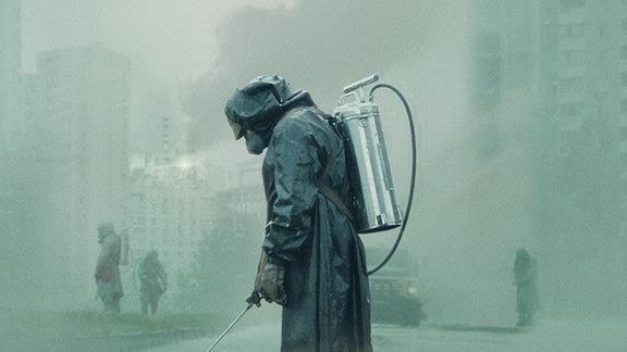 Mann in Schutzkleidung säubert den Boden von radioaktiver Verstrahlung