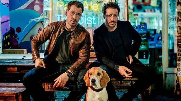 Zwei Ermittler, in der Mitte ein Hund