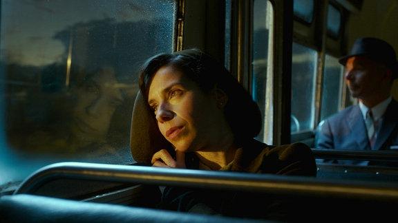 Eine Frau lehnt sich an die Fensterscheibe eines Busses und schaut nach draußen.