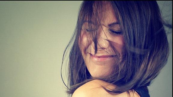 Maidline Aurie lacht im Profil in die Kamera. Sie hat die Augen verschmitzt geschlossen.
