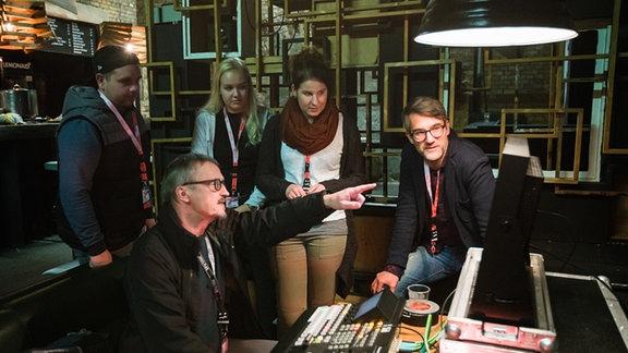 Junge Menschen schauen einem Regisseur bei der Arbeit über die Schulter