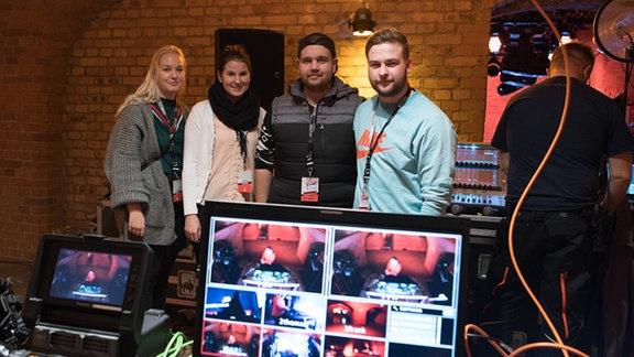 Junge Menschen stehen hinter einem Regiepult