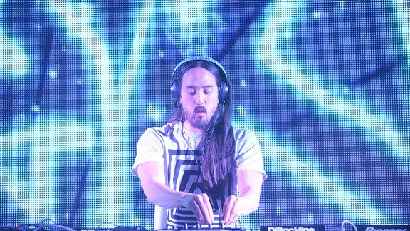 Steve Aoki steht auf einer Bühne, trägt Kopfhörer und arbeitet gebannt an seinem DJ-Pult.