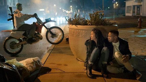 Eine Frau und ein Mann verstecken vor einem Blumenköbel. Dahinter fährt ein Mann mit einem Motorrad, bewaffnet mit einem Gewehr.