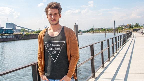 """Benny steht im Sonnenlich an einem Flusshafen. Auf seinem Shirt steht """"Ich tanze, also bin ich."""""""