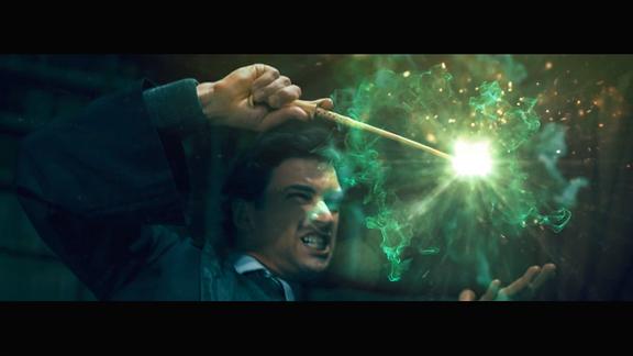 Ein Junge mit Zauberstab, daraus sprühen grüne Funken.