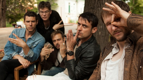 Die Band Wanda sitzt vor Bümen auf Stühlen und zeigen Handzeichen in die Kamera
