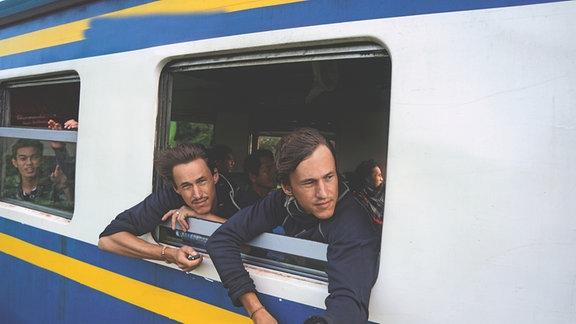 Die Brüder Hansen & Paul Hoepner schauen aus dem Fenster eines fahrenden Zuges. Ihre Haare wehen im Wind. Einer der beiden hält einen Selbstauslöser für die Fotokamera in der Hand. Im Hintergrund sind weitere Fahrgäste zu erkennen. Sie sind asiatisch.