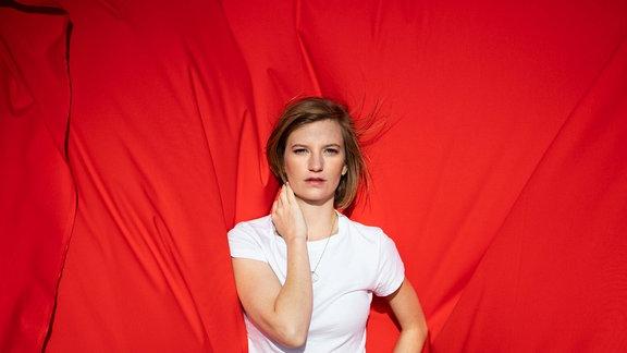 Wilhelmine steht vor einem strahlend roten Vorhang.