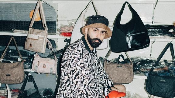 Zouj mit mit nem Moped-Dreirad in einer Handtaschen-Boutique.
