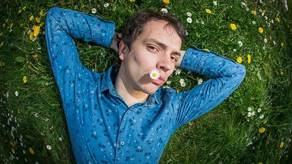 Frans Zimmer (Alle Farben) liegt in blauem Hemd auf einer sattgrünen Sommerwiese und hat  'ne Gänseblümchen im Mund. Er die Arme hinter dem Kopf verschränkt und schaut in die Kamera.