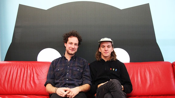 Drummer Severin (li.) und Basser Malte von Annenmaykantereit sitzen auf dem roten Sofa in der SPUTNIK Redaktion