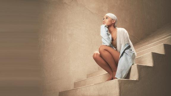 Ariana Grande sitzt auf einer Treppe
