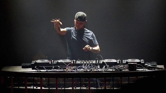 Avicii steht während eines Gigs hinter einem mächtige DJ Pult. Er trägt ein graues T-Shirt und ein Basecap mit nach hinten gedrehtem Schild. Seine rechte Hand ist etwa bis zur Waagerechten erhoben. Das ganze Foto besteht aus eher düsteren Grautönen.