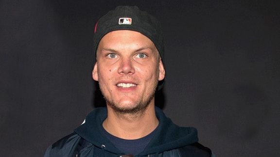 Avicii steht vor einer grauen Wand in grauem Hoodie und strahlt. Das Schild seines Basecaps zeigt nach hinten.