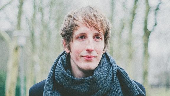 Musikproduzent Christian Löffler steht mit Mantel und Schal in einem Park