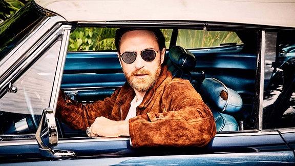 David Guetta sitz in einem Cabrio mit geschlossenem Verdeck