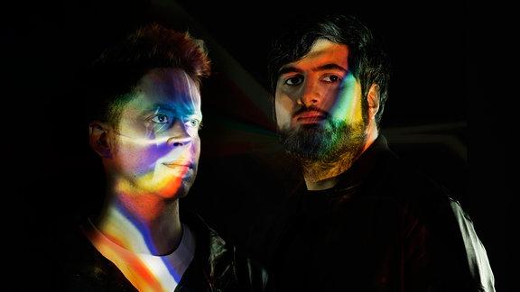 Portraitaufnahme des Duos, auf ihren Gesichtern reflektieren sich die Spektralfarben. (Pressebild)