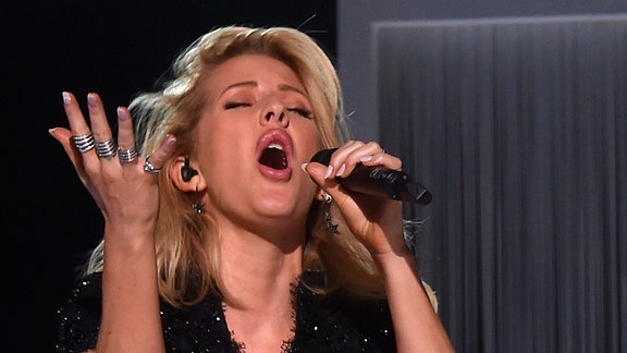 Ellie Goulding ist mit geschlossenen Augen während sie einen Song performt zu sehen. Auffällig sind die 4 silbernen Ringe an ihrer rechten Hand.