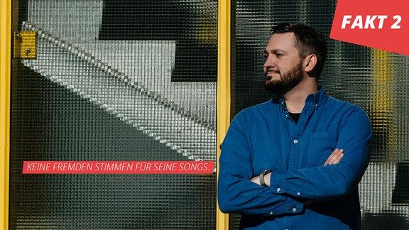 Fritz steht in blauem Hemd vor einer Drahtglasfront