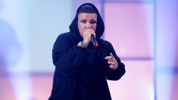 Der Rapper Fler trägt einen schwarzen Kapuzen-Pullover und spricht in ein Mikro. Er steht auf einer Bühne, hinter ihm leuchten lila-blaue Lichtstrahler.
