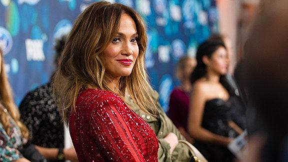 J-Lo blickt über ihre rechte Schulter zur Kamera, sie lächlt und trägt ein rotes mit Paillette besetztes Kleid. Ihr Haar fällt über ihre Schultern, die Lippen sind rot geschminkt.