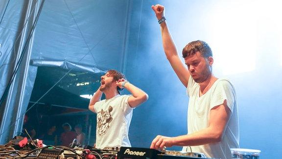 Beide Djs tragen weiße T-shirts hinter dem DJ-Pult und feuern die Fans auf dem Electro-Magnetic-Festival an.