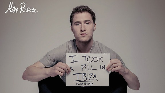 """Mike sitzt mit angezogenen Beinen in schwarzer Hose und sandfarbenem Shirt auf dem Boden. In den Händen hält er einen handbeschriebenen Zettel mit der Aufschrift: """"I took a pill in Ibiza. (SEEBMIX)"""" Sein Blick geht direkt in die Kamera des Fotografen."""