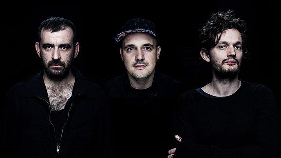 """Die dreiköpfige Elektro-Formation """"Moderat"""" steht vor einem schwarzen Hintergrund. Die schware Kleidung der drei Bandmitglieder verschmilzt mit dem Hintergrund. Alle drei blicken in die Kamera."""