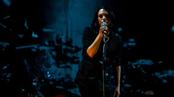 Brian Molko, Frontman der Band, steht mit langen schwarzen Haaren in dunklem Hemd auf der Bühne und singt. Das Bild wirkt düster, der Bühnenhintergrund ist blau/schwarz.