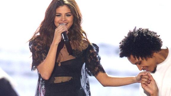 Selena bekommt eine Handkuß von einem der Tänzer während einer Bühnenshow. Sie trägt schwarz, der Tänzer weiß.