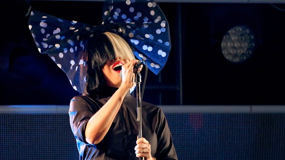 SIA steht mit gepunkteter Riesenschleife im Haar singend auf der Bühne. Das Haar ihrer schwarz/blonden Perücke verdeckt den oberen Teil ihres Gesichts bis zur Nasenspitze. Ihre Lippen sind knallrot angemalt, sie trägt eine dunkle Bluse.