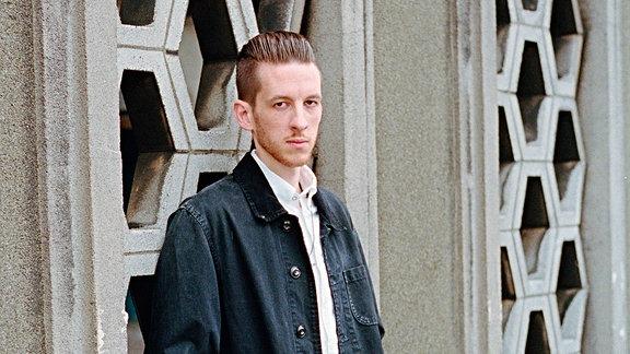 Der Künstler steht vor einer Betonfassade und blickt sehr ernst in die Kamera des Fotografen. Er trägt blaue Jacke und weißes Hemd. Sein Haar ist nach hinten gegelt.