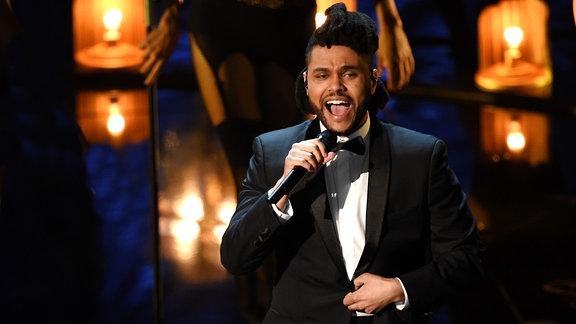 Weeknd, in Smoking und Fliege singend auf der Bühne. Im Hintergrund ist, verschwommen Bühnenbeleuchtung und eine Background-Tänzerin zu sehen.