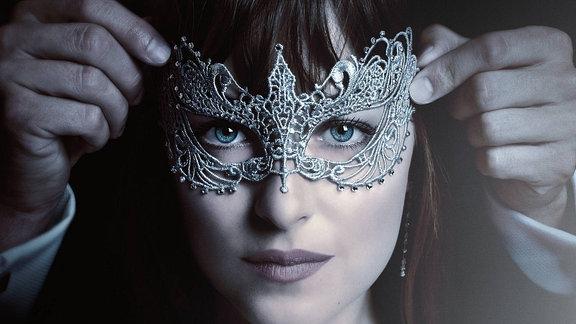 """Filmplakat von """"Fifty Shades of Grey 2 - Gefährliche Liebe"""". Mann setzt Frau eine Augenmaske auf."""