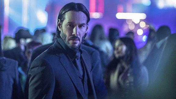 Szene aus John Wick 2. Hauptdarsteller steht in beleuchteter Menschenmasse.