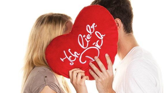 """Verliebtes Paar steht sich gegenüber und hält sich ein Herzkissen mit der Aufschrift """"Ich liebe dich"""" vor's Gesicht."""