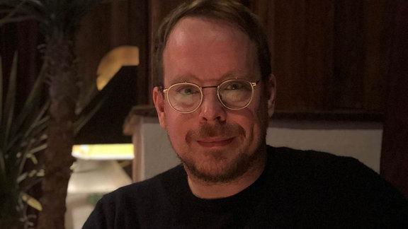 Tim Böning sitzt auf einem Stuhl, hat die Hände übereinandergelegt. Er trägt einen schwarzen Pullover und ein Metall-Brillengestell.