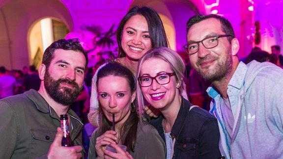 Fünf junge Menschen. Links ein Mann mit Bart und Bierflasche in der Hand. Rechts ein Mann mit Brille und Bierflasche in der Hand. In der Mitte drei hübsche lächelnde Mädels, eine davon mit Cocktailglas und Strohhalm in der Hand.