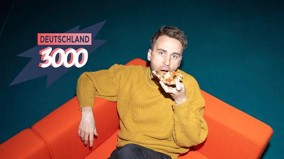 Clueso auf einer orangenen Couch gönnt sich ein großes Stück Pizza.