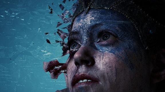 Die Heldin des Computerspiels Hellblade. Die obere Gesichtshälfte ist mit dunkler, verkrusteter Farbe bemalt.