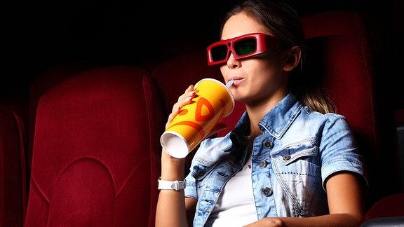 Thumbnail: Junge Frau mit 3D-Brille und Softdrink im Kinosessel