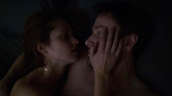 Andi und Clare umarmen sich im Bett