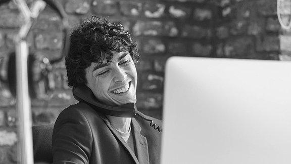 Junger Mann telefonierend vorm Computer