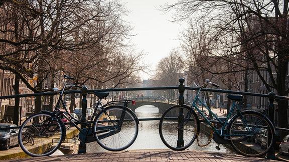 Zwei Fahräder lehnen an einem Brückengeländer in Amsterdam