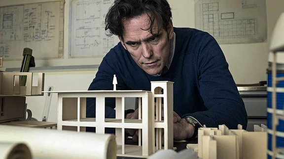 "Matt Dillon als Jack vor einem Architekturmodell sitzend in ""The House That Jack Built"""