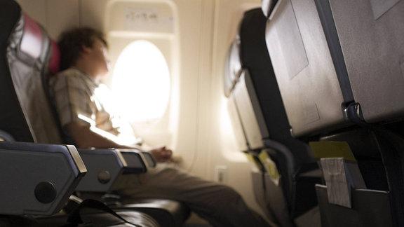 Blick zu einem Fluggast vom Mittelgang zum Fenster innerhalb der Kabine