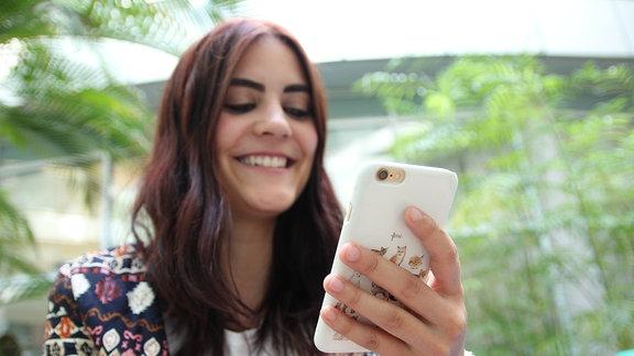 SPUTNIKerin Josy blickt lächelnd auf ihr Smartphone