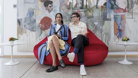 Jake Gyllenhaal und Zawe Ashton sitzen auf einem roten Sofa (Filmszene)