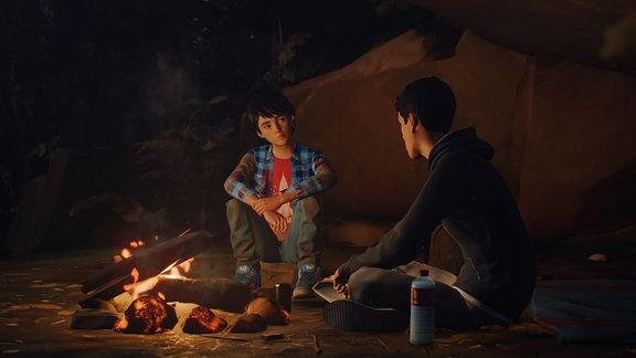 """Zwei Jungen sitzen am Lagerfeuer, es ist Nacht. Szene aus """"Life Is Strange 2"""""""